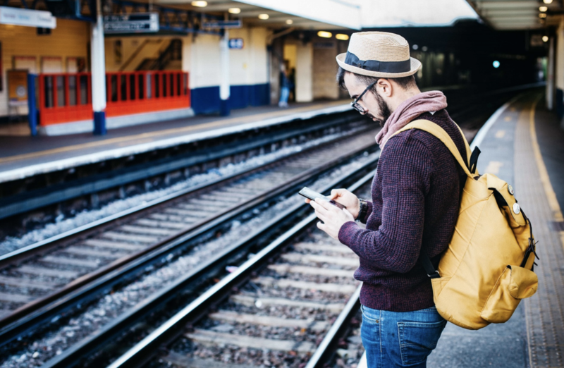 Male tourist using travel app on train station platform