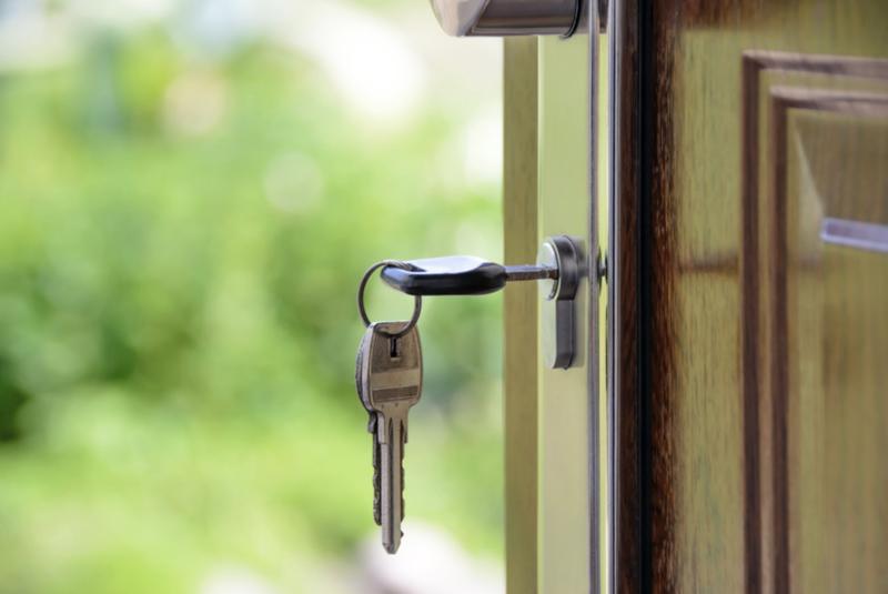 House key hanging in door lock