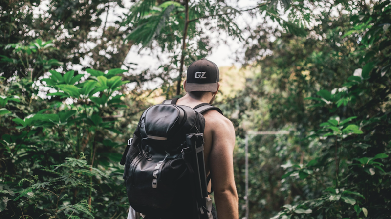 A man with a backpack hiking in the woods from behind