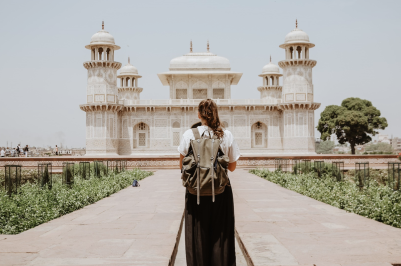 Girl with backpack facing away from camera standing before white historical building in Agra, India
