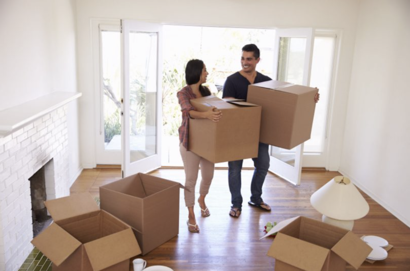 A couple moving their boxes into their new home