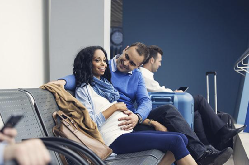 A pregnant woman and her partner about to board their flight.