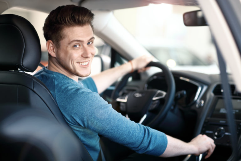 Happy young driver with cheap car insurance