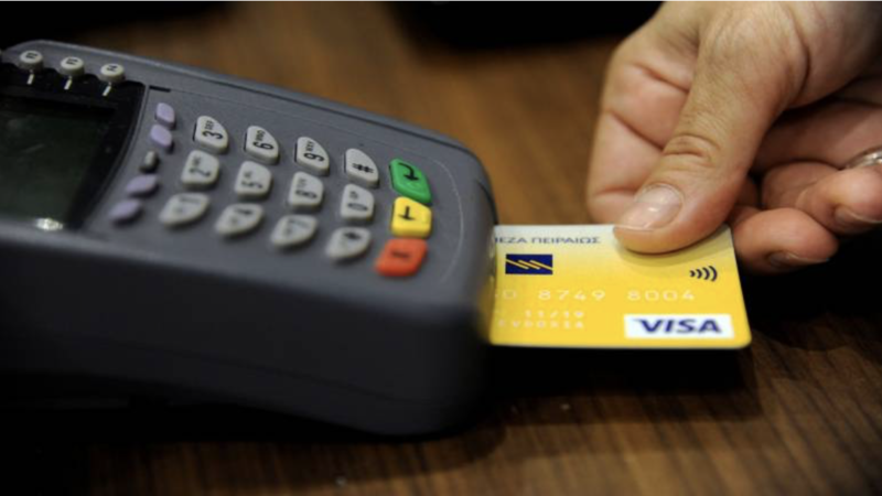 Man using his credit card overseas while incurring the currency conversion fee