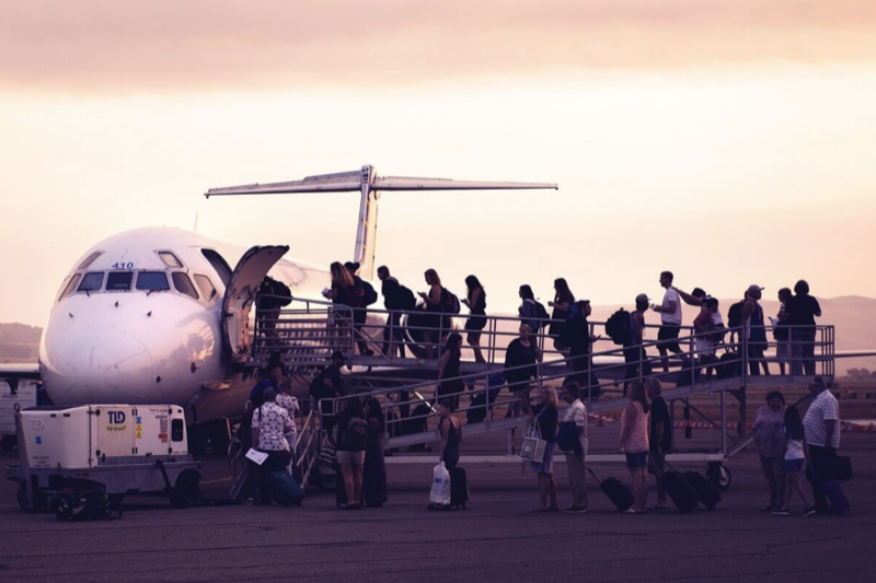 Travellers boarding plane at dusk